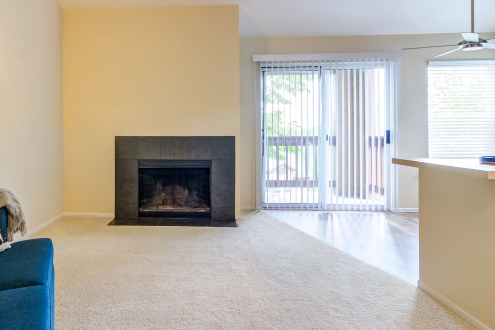 Fireplace and plush carpeting in a model home's living area at Sofi Lake Oswego in Lake Oswego, Oregon