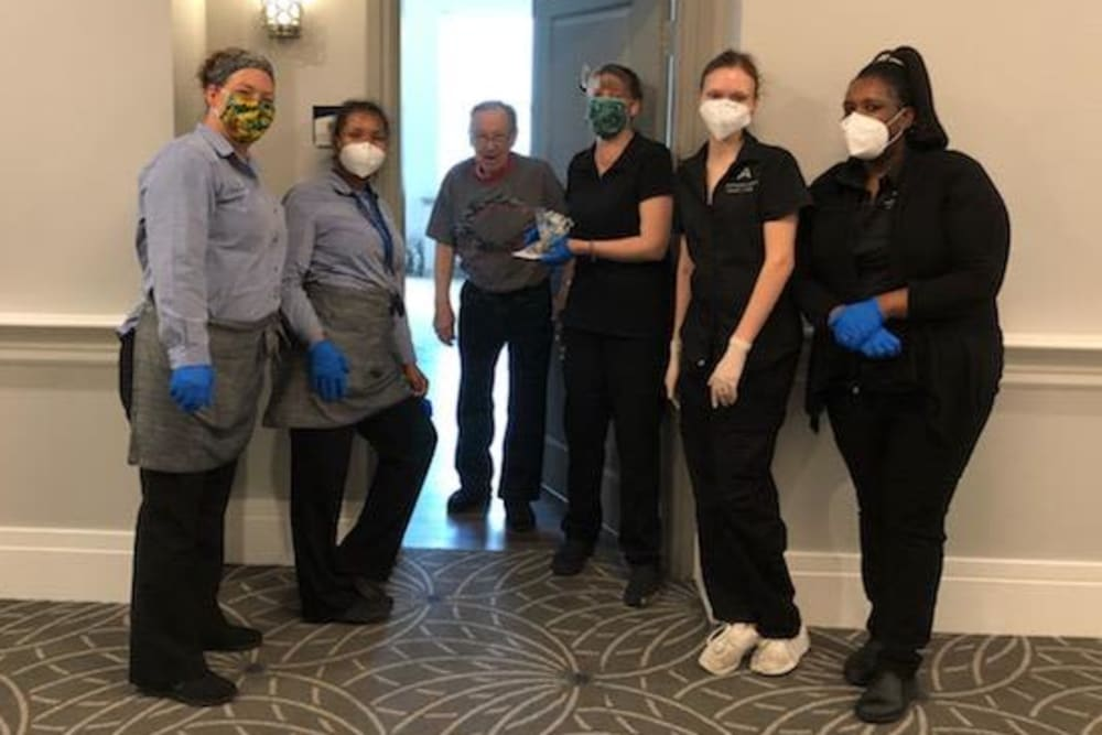 Group of masked caretakers greeting a resident at their door at a Anthology Senior Living community