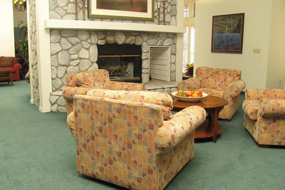 Cozy fireplace seating in the common area at Hilltop Commons Senior Living in Grass Valley, California