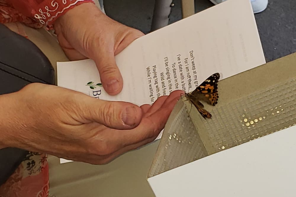 A woman holds a butterfly in hand at Landings of Blaine in Blaine, Minnesota