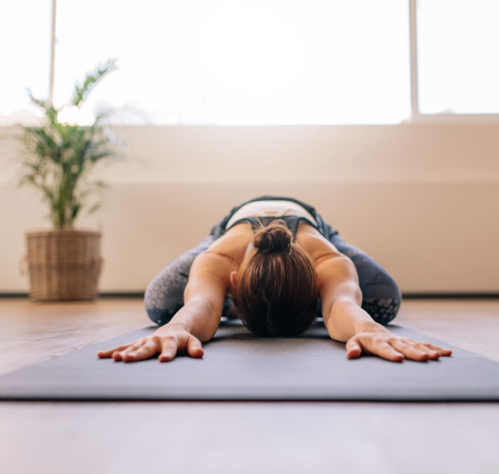 Resident stretching on a yoga mat in the onsite fitness center at Harbor Point Apartments in Mill Valley, California