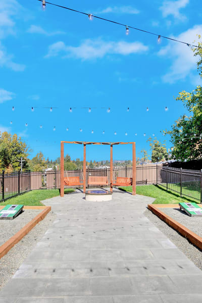corn hole courts and outdoor fire-pit swing at Park South Apartments in Seattle
