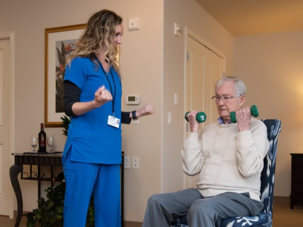 Nurse helping a resident with weights at Careage Home Health in Bellevue, Washington.