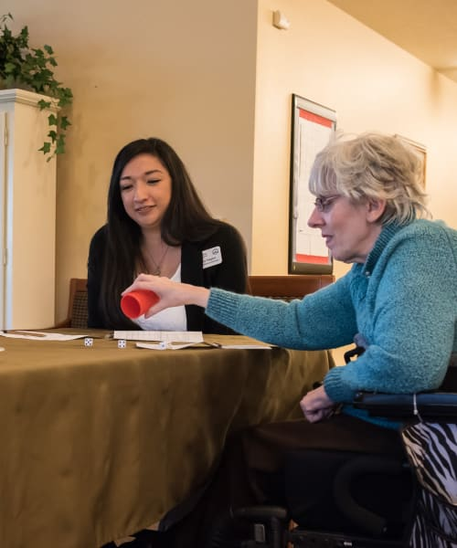 Resident and caregiver having a game night at The Springs at Willowcreek in Salem, Oregon