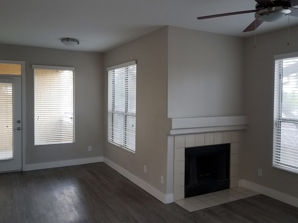 Hardwood floors and fireplace in model home living room at The Retreat Apartments in Phoenix, Arizona