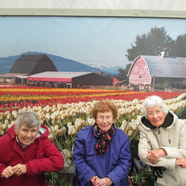 3 women standing in front of a mural of tulips at Quail Park of Lynnwood in Lynnwood, Washington