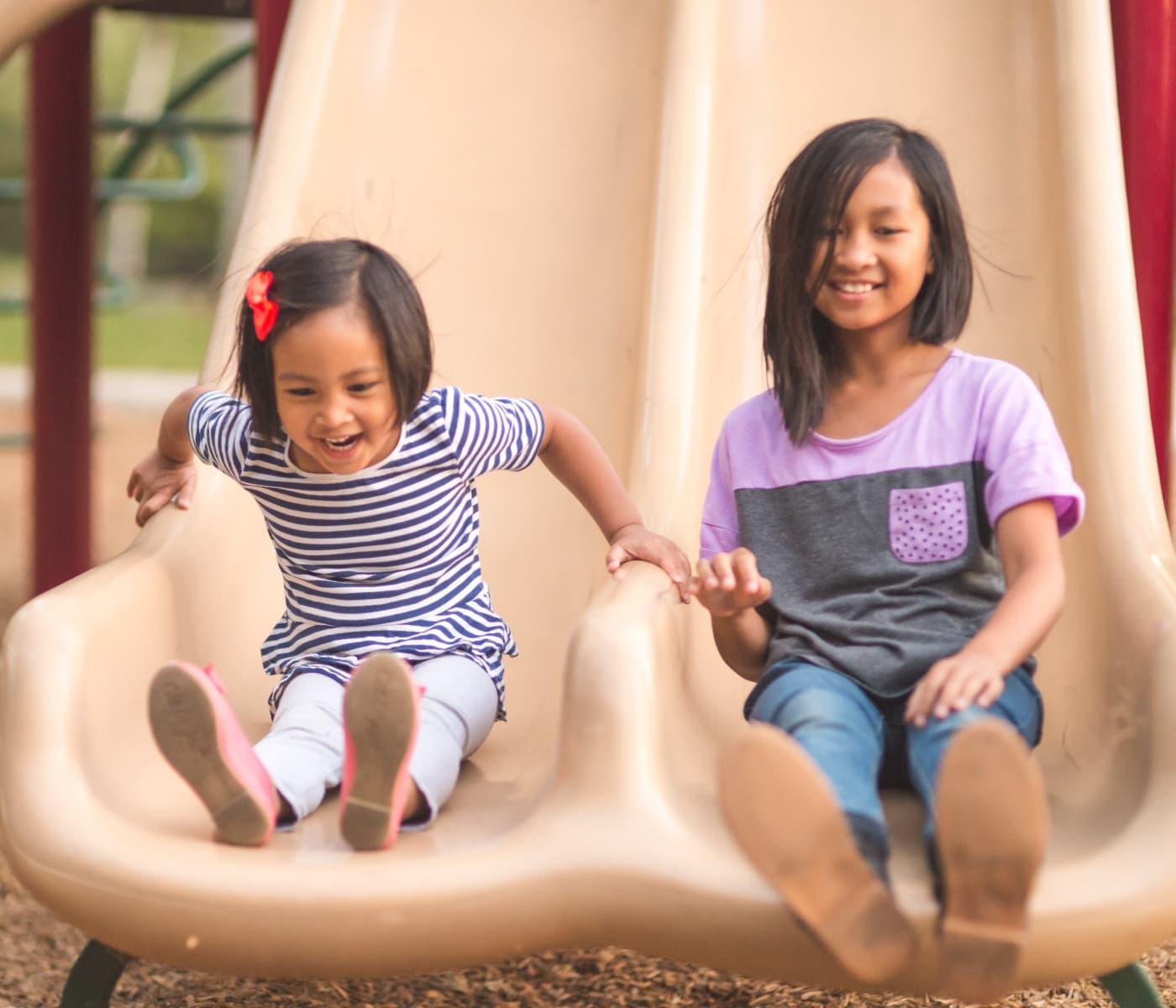 Little girls sliding at the park in Alexandria, Virginia near Mount Vernon Garden Apartments