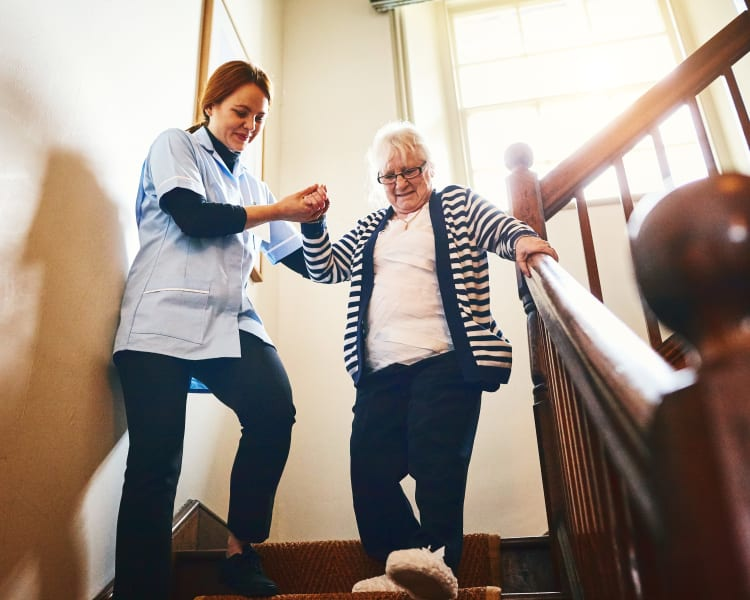 A caregiver assisting a resident down the stairs at Harmony Senior Services in Charleston, South Carolina
