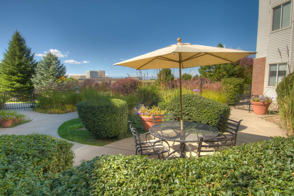 Outdoor garden with umbrella and seating at Caley Ridge Assisted Living in Englewood, Colorado