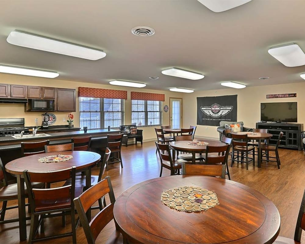 Activity room with TV and kitchen at Milestone Senior Living in Tomahawk, Wisconsin.