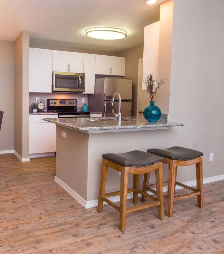 Granite countertops and wood floor in a kitchen at Carrollton Park of North Dallas in Dallas, Texas