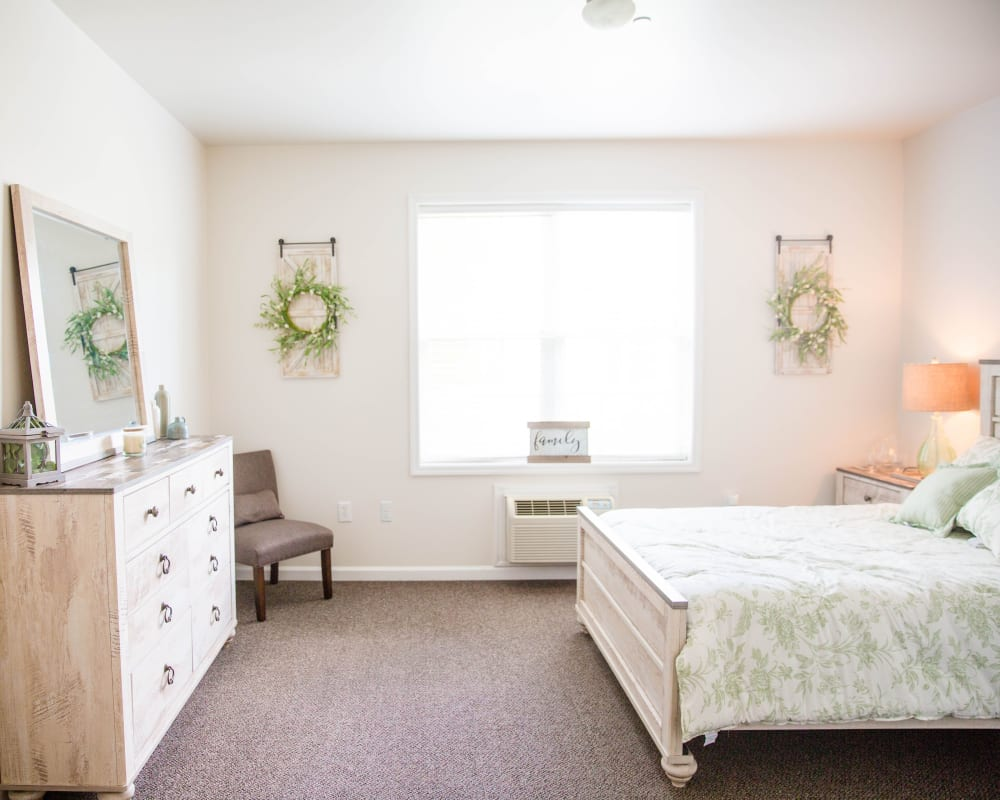 Spacious bedroom with wall art and dresser at Arcadian Cove in Richmond, Kentucky.