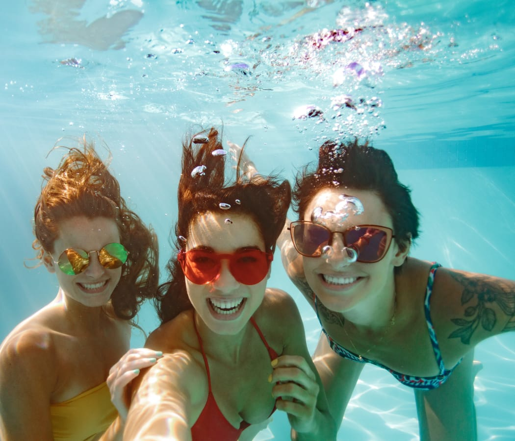 Cheerful friends swimming underwater in pool at Village Green of Bear Creek in Euless, Texas