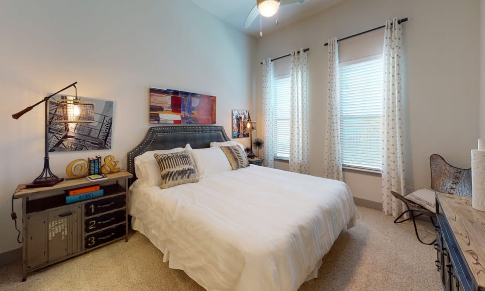 Bedroom with carpet and two large windows for lots of light at Bellrock Upper North in Haltom City, Texas