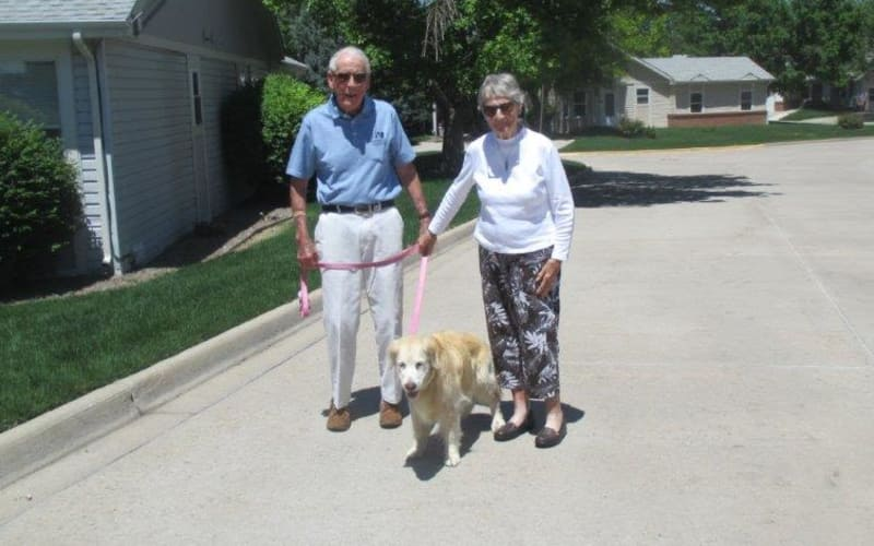 Happy senior couple walking their dog at Eastern Star Masonic Retirement Campus in Denver, CO