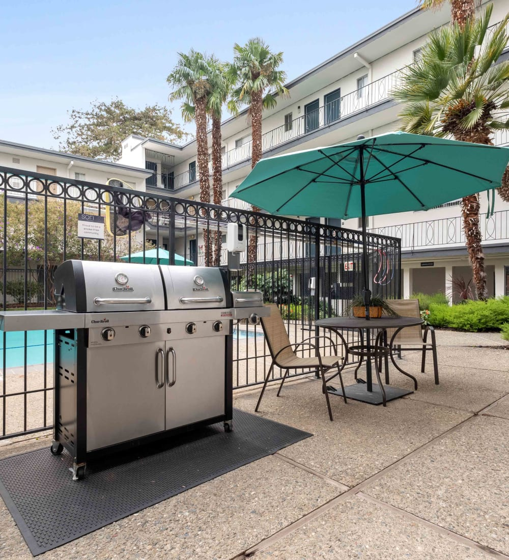 Palm trees and beautiful flora near the barbecue area with gas grills at Sofi Redwood Park in Redwood City, California