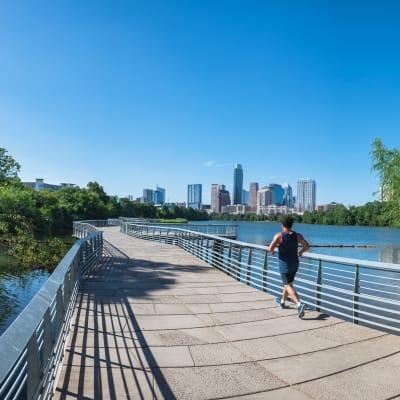 Man running on bridge overlooking downtown Austin near Marquis at Barton Trails in Austin, Texas
