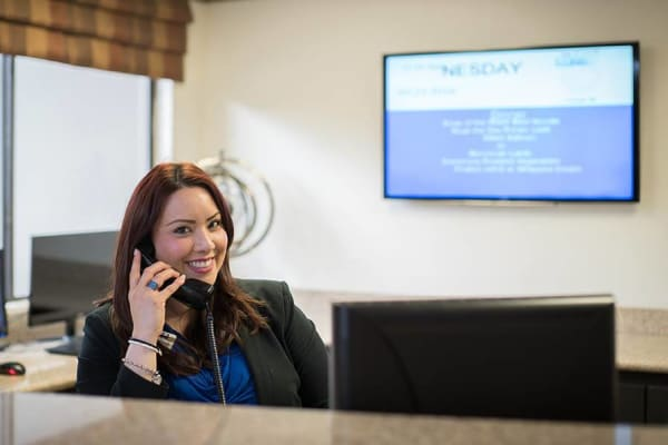 Happy receptionist working at Pasadena Highlands in Pasadena, California