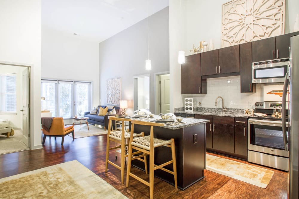 Bright and open kitchen island with tall wood chairs overlooking living room at Marq Midtown 205 in Charlotte, North Carolina