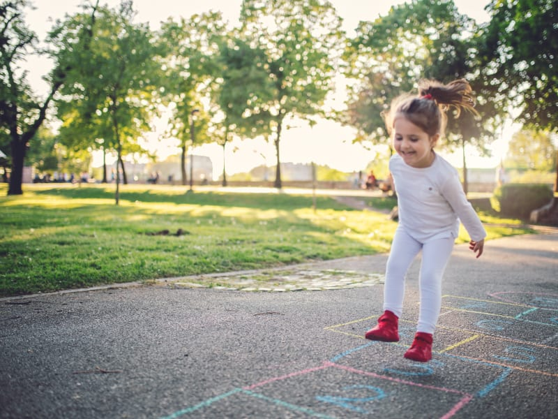 Child playing hopscotch at The August Apartments in Lexington, Kentucky