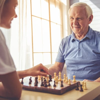 Resident playing chess with his daughter at Westminster Memory Care in Aiken, South Carolina