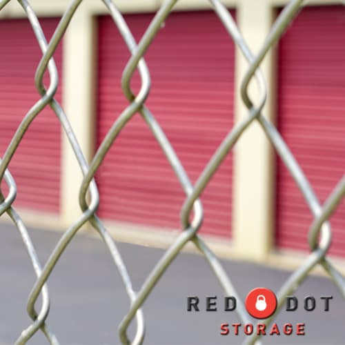 Chain link fence in front of climate-controlled storage units at Red Dot Storage in Rockford, Illinois