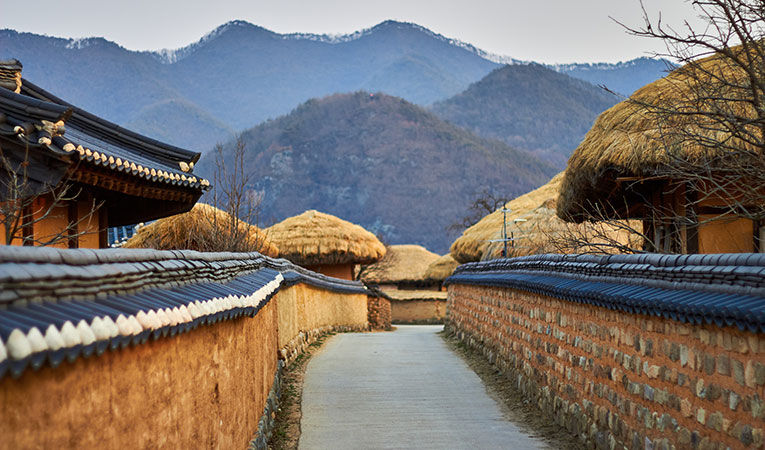 Looking down a walled path with straw roofs and mountains in Andong, South Korea