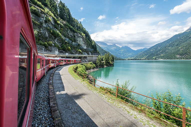 train through the countryside next to a blue lake