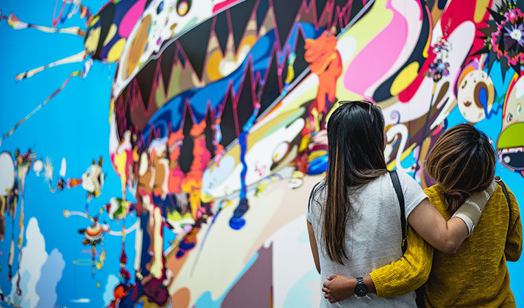 Two girls hugging by a mural