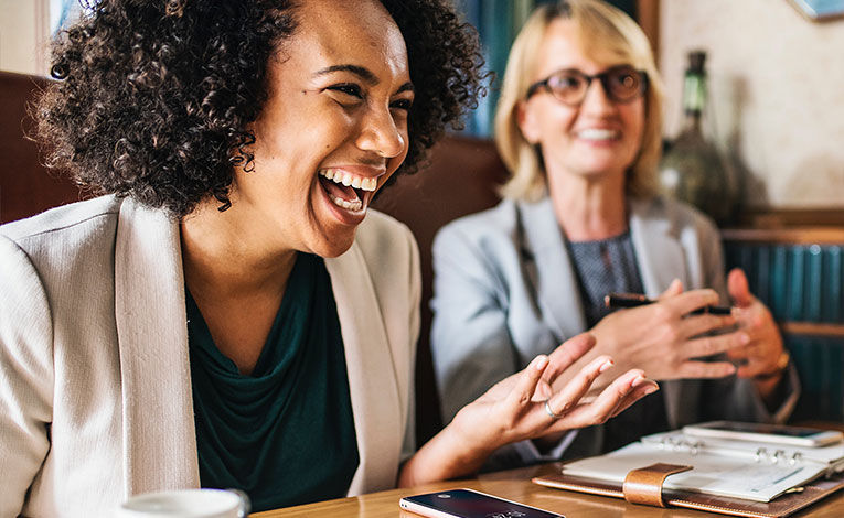 Woman laughing at a meeting/coffee date with friends