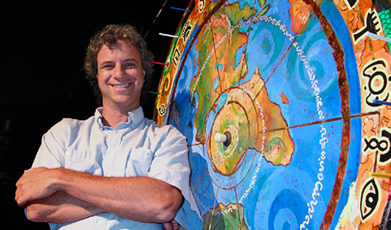 Jeff Greenwald with a big wheel of the world