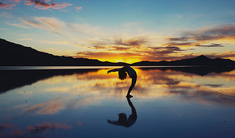 Woman doing a yoga pose on the beach at sunset
