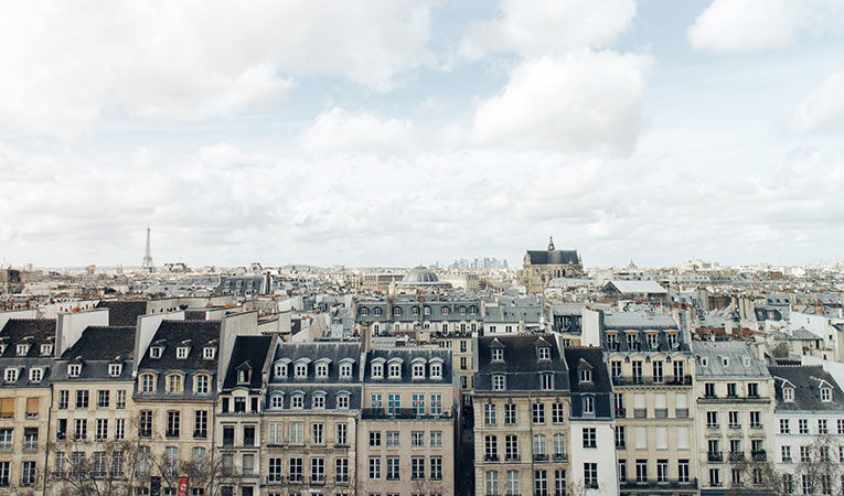 Skyline of parisian buildings with eiffel tower in the background and big white clouds