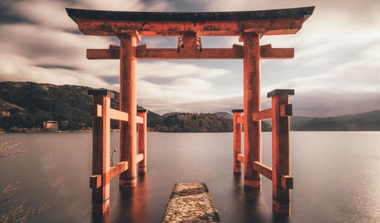 A orange torii gate in a lake