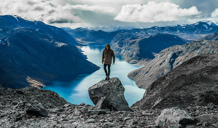 Man standing on mountain cliff in Norway