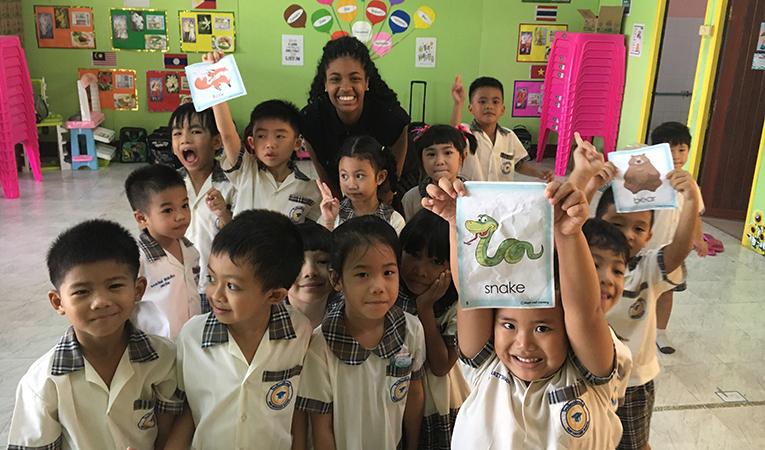 Girl poses with her ESL students in Asia