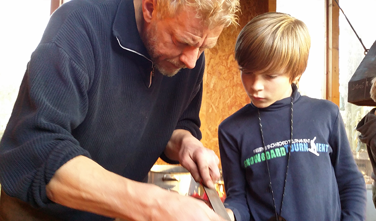 old man showing a young boy how to use a tool