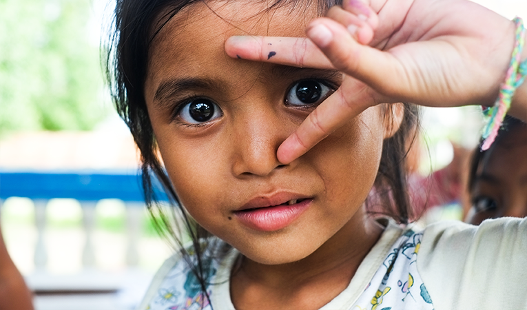 Young brown girl holding up peace sign