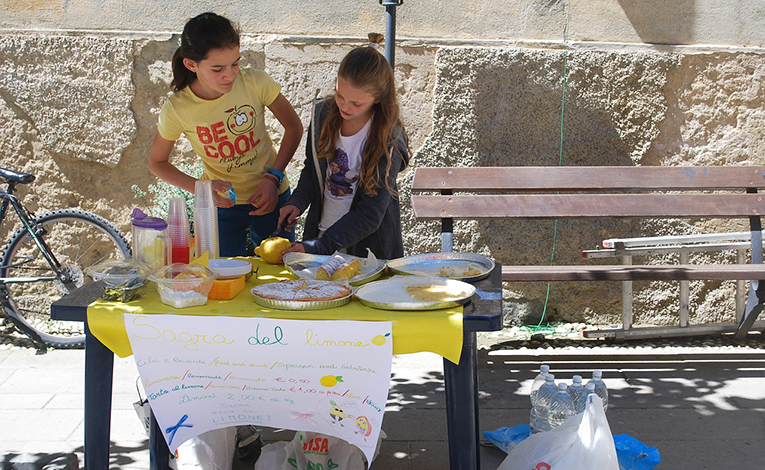 Two girls standing at a lemonade stand