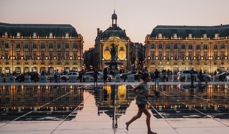 Night in Bordeaux, girl running across plaza