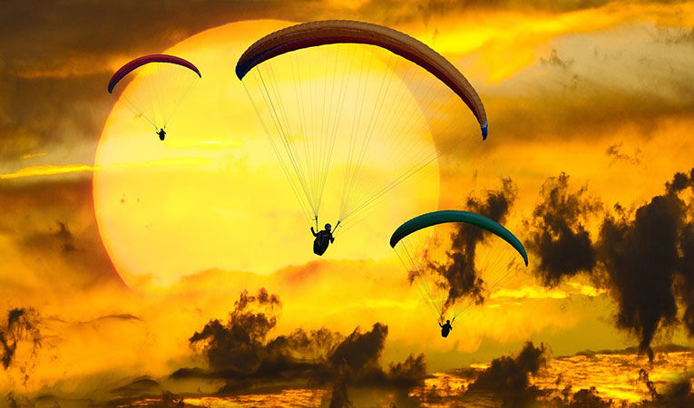 Paragliders Glide In Front Of A Huge Yellow Sun