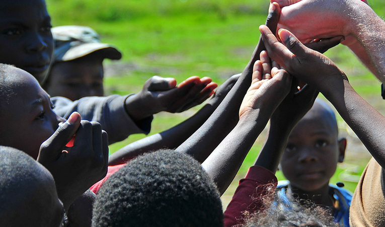 Children in Haiti holding out their hands