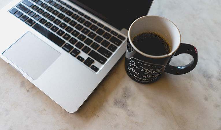 how to get tefl certification online. Mac laptop on table with a cup of coffee.