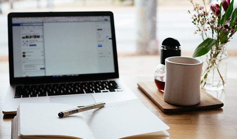 how to get tefl certification online. Open laptop and notebook with a cup of coffee.