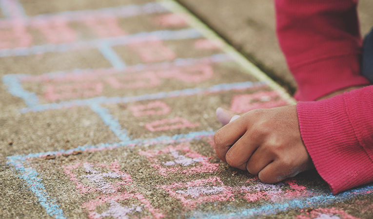 how to get tefl certification online. Close up of girl in pink sweater drawing with chalk on sidewalk.