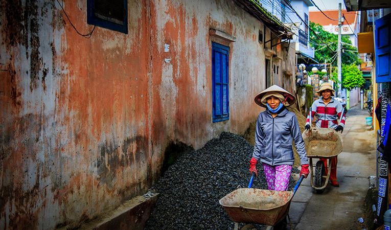 women walking with wheelbarrows through alley