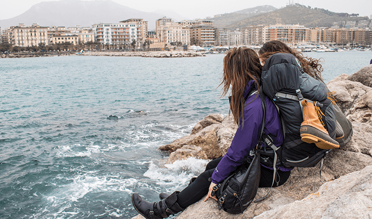 Backpackers sitting on the rocks off the coast of Italy
