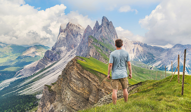 man standing looking at the Dolomites, Italy