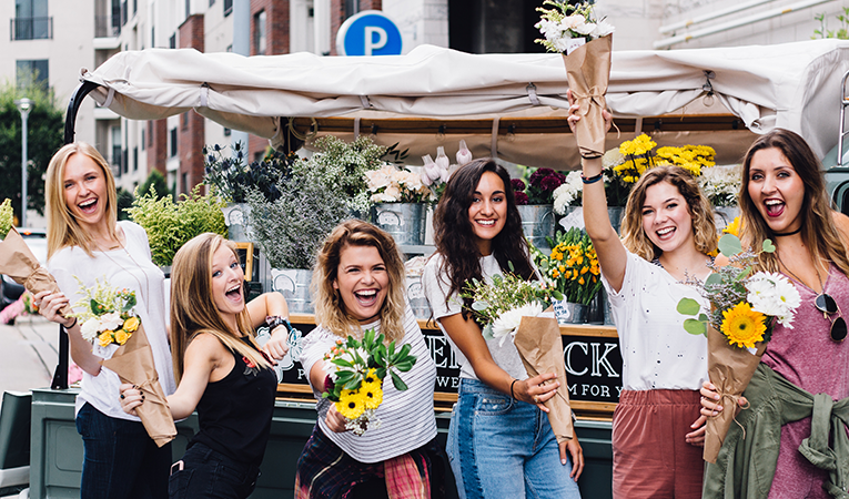 group of girls posing with flowers at market