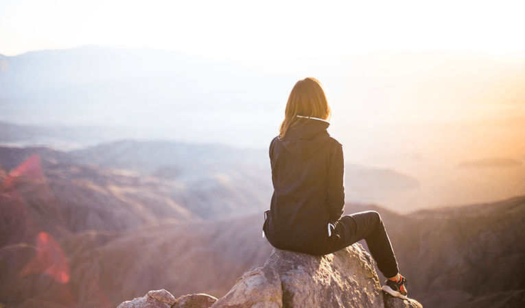woman sitting on rocky peak at sunrise
